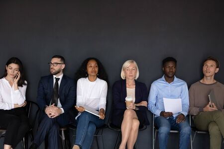 Multicultural business people six applicants feel afraid or tedium waiting turn for job interview sitting in queue on chairs on black wall background, human resources head hunting, work search concept