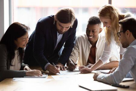 Fröhliche, vielfältige Mitarbeiter, die gemeinsam mit Dokumenten arbeiten, Projektstatistiken lesen, Kolleginnen und Kollegen lächeln, die an Teamarbeit beteiligt sind, Strategien bei Unternehmenstreffen entwickeln, reden, Brainstorming Standard-Bild