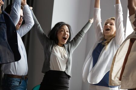 Happy business people celebrating teamwork success and triumph together, achievement, screaming with joy at meeting, diverse employees colleagues received good news, rejoicing victory in office Stock Photo