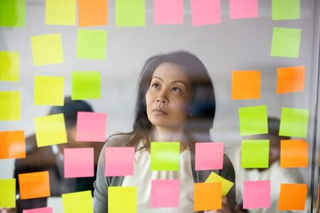 Chef d'équipe d'une femme d'affaires asiatique sérieuse lisant des tâches ou des idées de démarrage sur des papiers collants, regardant des notes sur un mur de verre, un coach mentor planifiant un projet d'entreprise sur un tableau de bord au bureau Banque d'images