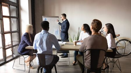 Boss stands near flip chart presents topic to audience, demonstrate stats, diverse staff attending at training, introduction of new idea or company products, reporting work result for partners concept