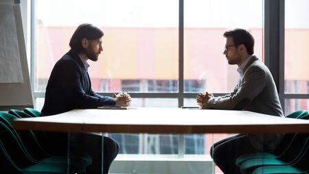 Deux hommes d'affaires sérieux assis en face à table dans la vue latérale de la salle de réunion, confrontation commerciale et concept de négociation difficile, débat sur le dialogue des opposants, concurrents se regardant