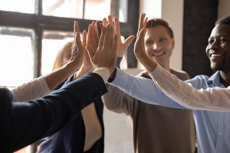 Close up palms of motivated different ethnicity business people mates raised hands giving high five 5 gesture, co-workers celebrating project accomplishment, sales increase, great work results concept