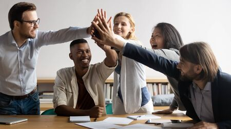 Excited diverse business team giving high five at meeting, laughing and smiling employees celebrating good teamwork result, achievement, happy businesspeople engaged in team building activity Stock Photo
