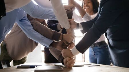 Diverse workers involved in teambuilding activity having fun at office boardroom, happy affiliates stacked fists together close up, engaged in motivational training, unity support team spirit concept