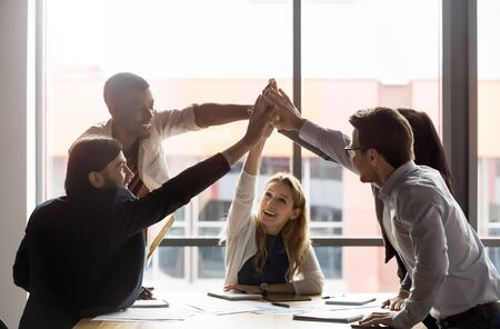 Happy diverse employees team giving high five, sitting at table in boardroom, celebrating good teamwork result, business achievement, smiling happy businesspeople engaged in team building activity