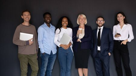 Near black wall studio background group of intelligent multiethnic coaches corporate staff ready for work negotiations hold gadgets look at camera, successful specialists professional team, hr concept