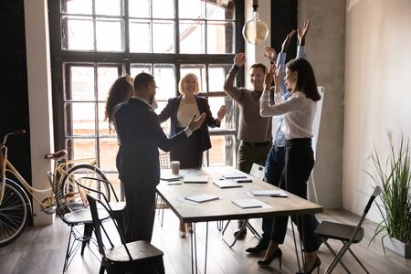 Six excited multi-ethnic staff celebrating project accomplishment raise hands feels happy sharing common success standing in office boardroom ending meeting or seminar got great business news concept