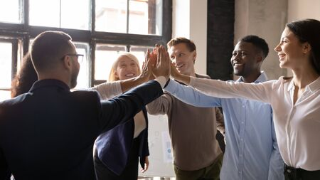 Horizontal banner group of happy successful multi ethnic workmates stacked hands palms together giving high five celebrating career growth feels enthusiastic and motivated for new achievements concept Stock Photo