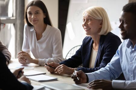 Multiracial smiling businesspeople participating at group meeting sitting at boardroom desk, interested multi-ethnic partners staff team members listening fresh creative new ideas at briefing activity Stock Photo