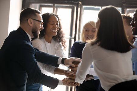 Multiracial entrepreneurs stacked hands together at group meeting celebrating common victory sharing successful project accomplishment, teambuilding activity team spirit, corporate staff power concept Stock Photo