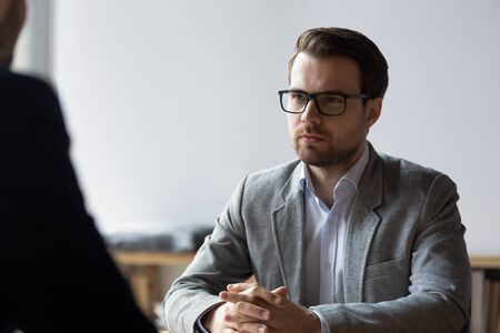 Serious businessman wearing glasses sitting with clasped hands, looking at opponent at difficult negotiations, business confrontation and disagreement concept, opponents competitors dialogue debate