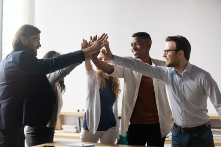 Excited successful diverse business people giving high five, celebrating win, achievement, good teamwork result, happy employees team engaged in team building activity at corporate meeting
