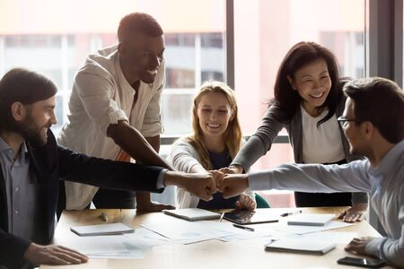 Happy diverse employees team joining fists, sitting at table in boardroom, smiling colleagues celebrating success, good teamwork result, business achievement, engaged in team building activity
