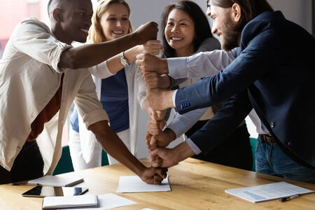 Happy diverse employees stack fists at corporate meeting, celebrating success, business achievement, engaged in funny team building activity, smiling colleagues showing unity and support Stock Photo