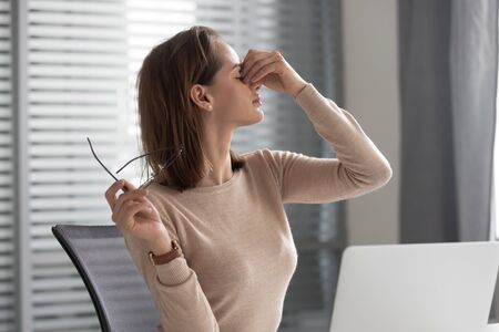 Exhausted young female worker sit at workplace massage eyes suffering from migraine or headache, tired businesswoman take off glasses having blurry vision or dizziness overwork at laptop in office Reklamní fotografie - 140304659