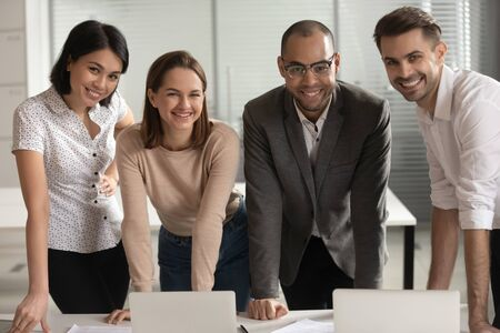 Happy multiethnic mixed young colleagues look at camera working together at workplace in office, smiling diverse multiracial coworker employee engaged in teambuilding activity. Collaboration concept