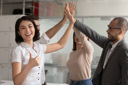 Excited biracial millennial female employee show thumb up engaged in teambuilding activity with coworkers give high five for shared success, unity and support together. Cooperation concept Stock Photo