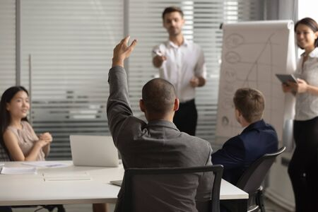 Back view of male employee raise hand take part in flip chart presentation discussion at office meeting, man group leader ask question to coach or tutor during whiteboard training with colleagues