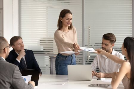 Smiling female employee share handout materials to coworkers during team meeting in office, woman worker give printed paperwork statistics or company financial report at corporate briefing