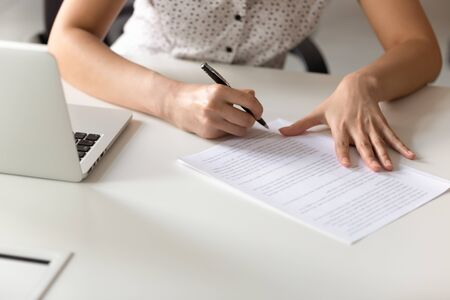 Close up of concentrated female employee busy writing letter at workplace, focused woman editor sit at desk reading letter or document make corrections, handwriting check paperwork report