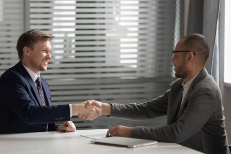 Happy diverse businessmen handshake closing deal congratulate with successful negotiations, smiling business partners shake hands greeting or thanking for interview talk in office. Cooperation concept Foto de archivo