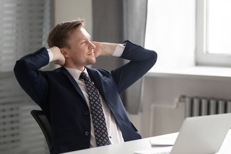 Thoughtful businessman lean back relax in chair at workplace look in distance dreaming of career opportunities, dreamy male employee take break visualizing or imagining. Business vision concept