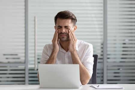 Tired businessman with at workplace massage eyes head feel unwell having strong headache or blurry vision, exhausted male employee suffering from dizziness overwork at laptop. Health problem concept Reklamní fotografie - 140303327