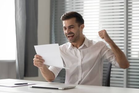 Overjoyed male employee sit at workplace feel euphoric receive post letter with great amazing news, excited man worker triumph read paperwork correspondence stunned get promoted. Success concept Stock fotó