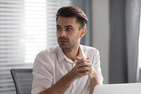 Focused male employee sit at workplace look to side listen to someone talking in office, thoughtful pensive man worker distracted from work interested in coworker or colleague conversation Foto de archivo