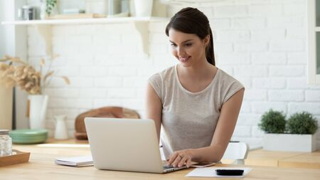 Smiling young woman sit at desk in kitchen working on laptop gadget, happy millennial girl manage finances pay household expenditures or taxes online, use Internet banking services on computer Stock fotó