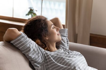Head shot peaceful tranquil attractive young woman crossed hands behind head, taking pause break on cozy couch. Mindful dreamy pretty millennial lady relaxing on comfortable sofa alone at home.