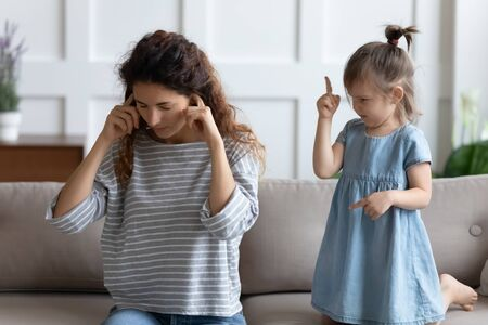 Stressed young mother covering ears with fingers, annoyed by bad daughters behavior in living room. Unhappy small preschool girl shouting, irritating frustrated mommy at home, family problems concept.