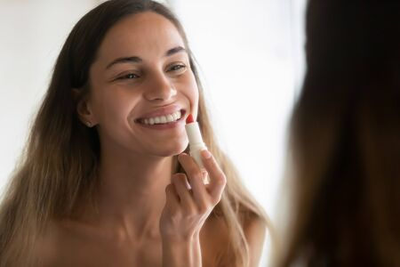 Smiling young beautiful Caucasian woman look in mirror do morning makeup paint lips in bathroom, happy millennial girl get ready in home bath apply red moisturizing lipstick, beauty routine concept Stock fotó