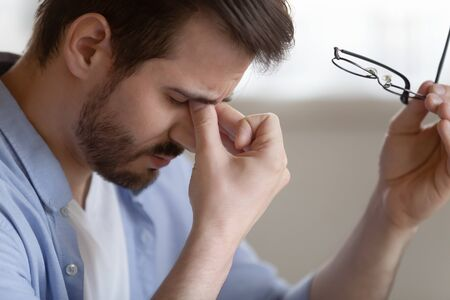 Exhausted Caucasian millennial man take off glasses feel fatigue overwhelmed with work struggle with blurry vision, tired young male massage eyes suffer from headache or migraine, eyesight problems Reklamní fotografie