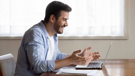 Happy millennial Caucasian worker sit at desk work on laptop from home read good pleasant news in internet, smiling overjoyed young man feel euphoric triumph use computer win lottery online