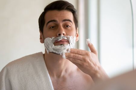 Young Caucasian man look in mirror apply shaving foam on face after taking shower in modern bathroom, millennial male do skincare daily facial routine procedure in home bath, personal hygiene concept Stock fotó - 140305232