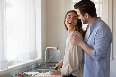 Loving young husband hug from behind beautiful millennial wife cooking chopping vegetables, happy newlywed couple cuddle enjoy romantic morning preparing food in kitchen at home together