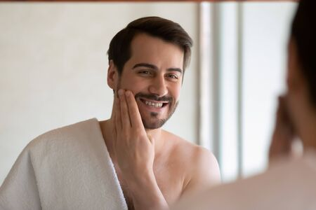 Smiling Caucasian millennial man in towel look in mirror apply face lotion after shaving in home bathroom, happy young male do daily skincare facial routine treatment in bath, hygiene concept