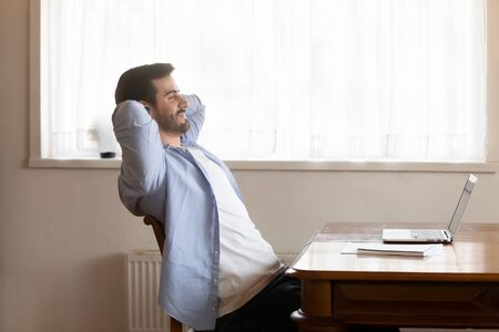 Calm Caucasian millennial man lean back in chair hands over head look in distance dreaming or thinking, happy male worker distracted from work take break relaxing stretching at desk at workplace