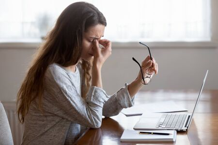 Exhausted young woman sit at table work on laptop take off glasses suffering from blurry vision or dizziness, tired millennial girl feel fatigue massage eyes having sudden headache or migraine