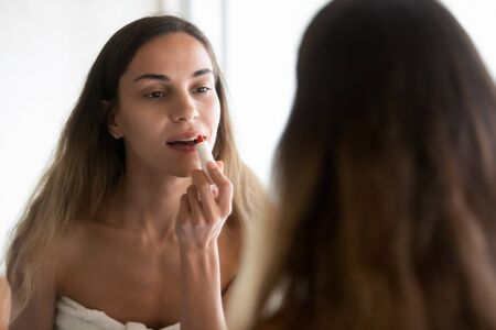 Beautiful millennial girl in towel look in mirror get reading in morning apply red lipstick, Caucasian young woman do makeup paint lips after shower in home bathroom, beauty care routine concept