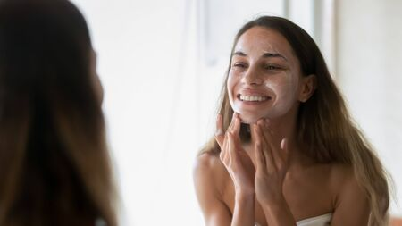 Happy millennial girl look in mirror after shower in home bath do facial scrub mask massage skin, smiling young woman perform daily face morning routine or beauty procedures in bathroom