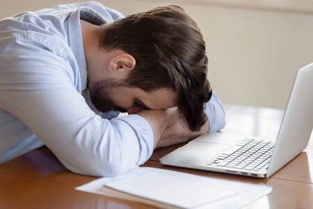 Tired Caucasian young male worker have sleep deprivation take nap at table overwhelmed with computer work, exhausted millennial man fall asleep sitting at desk feel fatigue overwork on computer