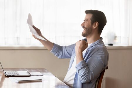 Overjoyed millennial man sit at desk work on laptop get read good news in postal letter, excited happy young male worker receiver pleasant post notice, job promotion mail or positive agreement