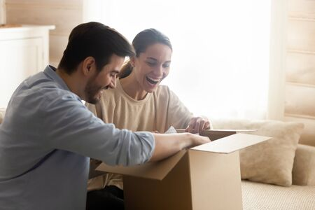 Overjoyed millennial couple feel euphoric open cardboard package buying goods shopping online together, happy young husband and wife unwrap order like good quality internet delivery service