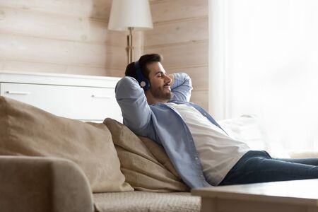 Calm millennial Caucasian man lying relaxing on comfortable couch in living room listen to music in earphones, young male rest on cozy sofa at home enjoy good quality sound in modern headphones