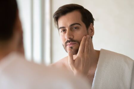 Young Caucasian man look in mirror do skincare facial routine after shower in home bathroom, millennial male in towel after bath apply face lotion or cream on skin after shaving, hygiene concept