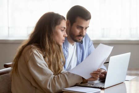 Concentrated young husband and wife hold paperwork busy paying household bills or taxes on laptop online, focused millennial married couple manage finances, use internet banking service on computer