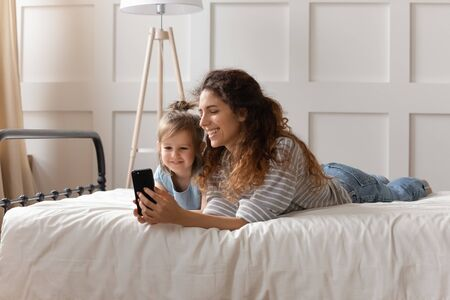 Full length smiling little preschool child daughter posing for mobile selfie shot with pleasant mother, lying together on comfortable bed. Happy bonding family watching funny cartoons on smartphone.